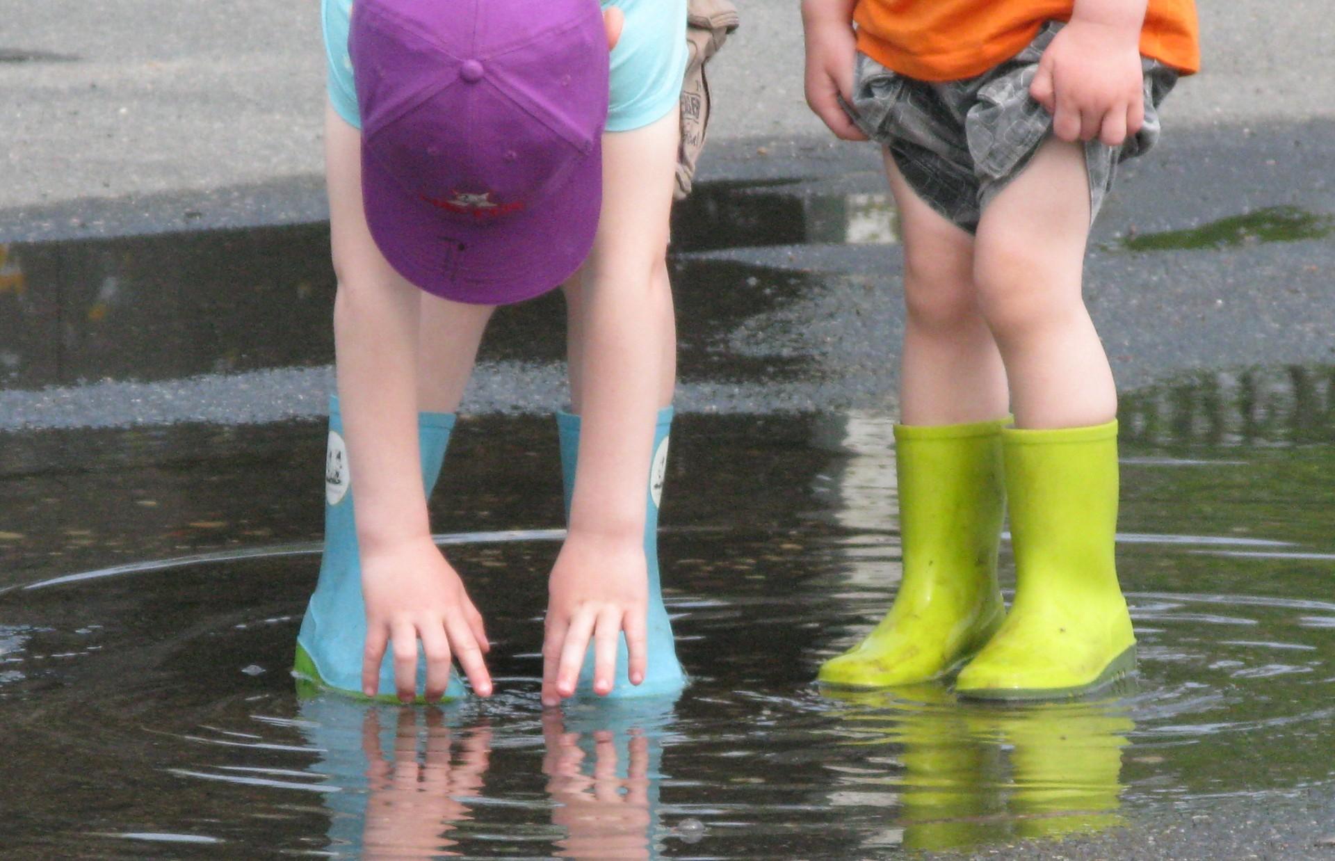 kinderen met felgekleurde laarzen in een plas water