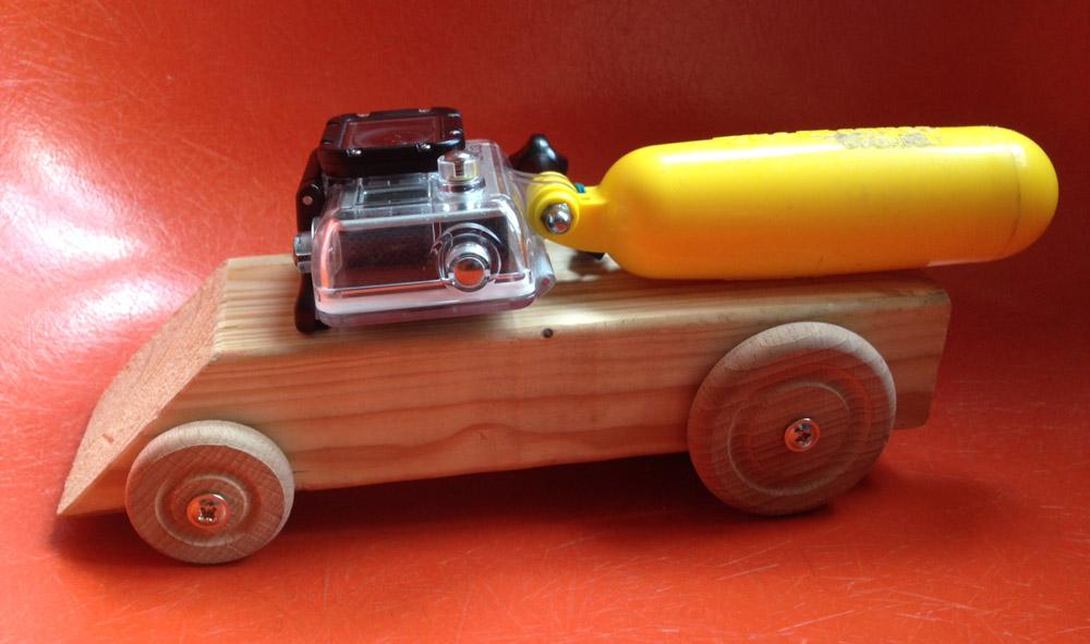 houten auto, met actionacm op het dak en gele drijver op oranje achtergrond