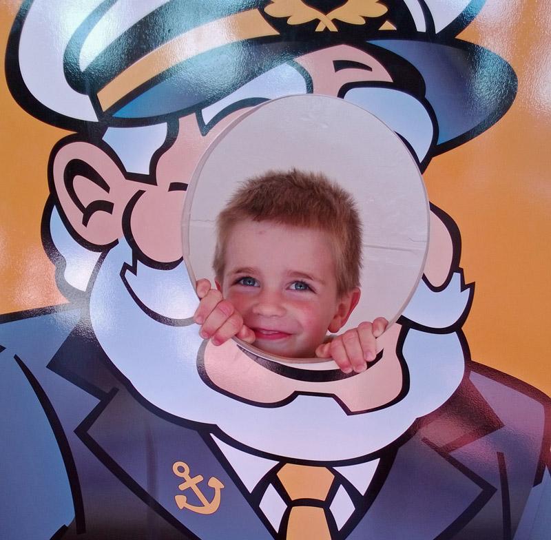 Glunderend jochie poseert als kapitein op SS Rotterdam.