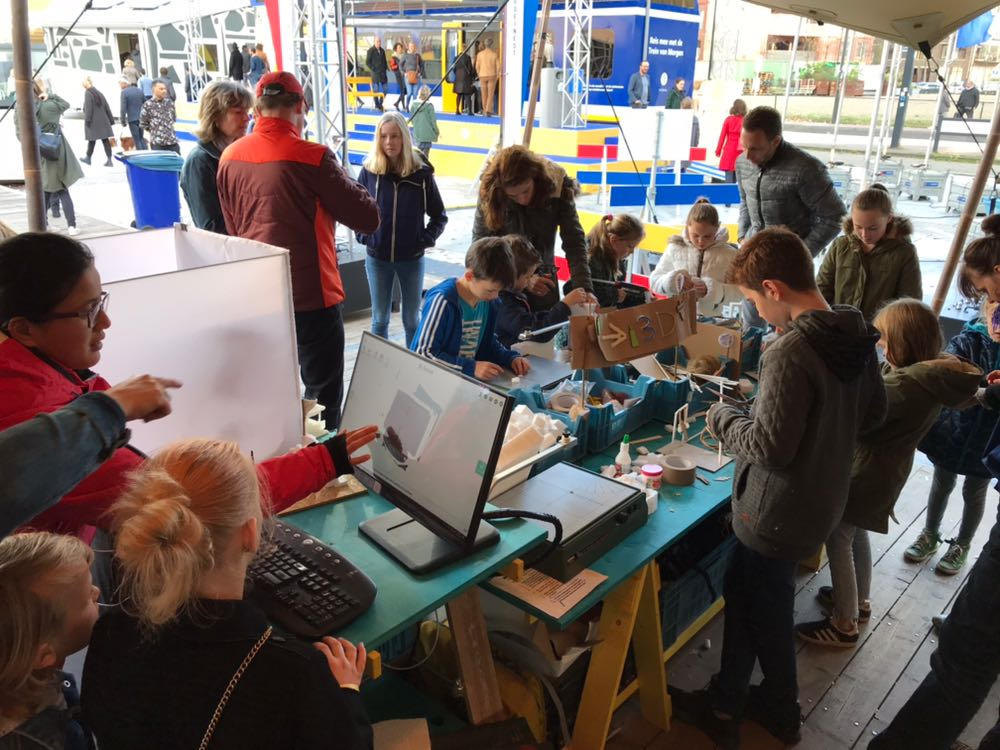 tafels vol computers, hout, en jonge makers er omheen.