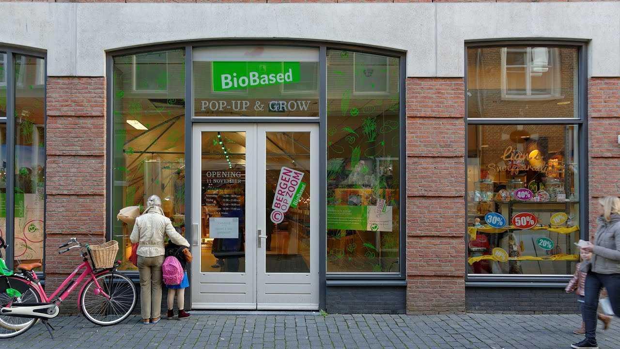 Vrouw en meisje, naast roze fiets, kijken naar de etalage van winkelpand Pop-Up & Grow.