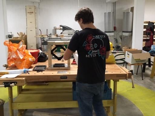 Boris in de werkplaats van Omlab, op de rug gezien