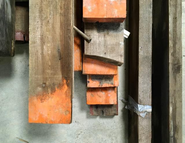stapel oude plafondbalken met oranje menie op de kop